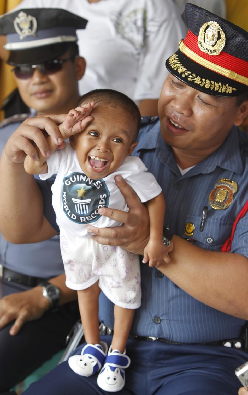 "A police officer holds on his lap Junrey Balawing, the ""World's Shortest Living Man"" declared by the Guinness World Records in Sindangan"