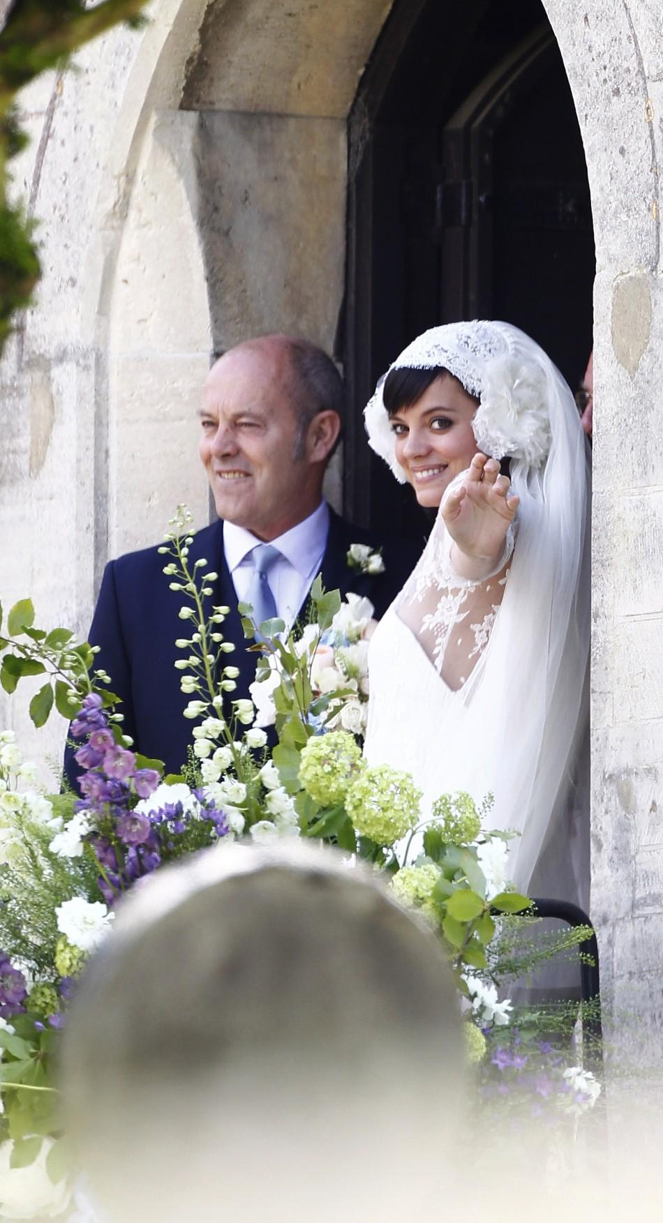 British singer Lily Allen (R) smiles after marrying Sam Cooper as the couple leaves St James the Great Church in Cranham, Goucestershire, western England, June 11, 2011.