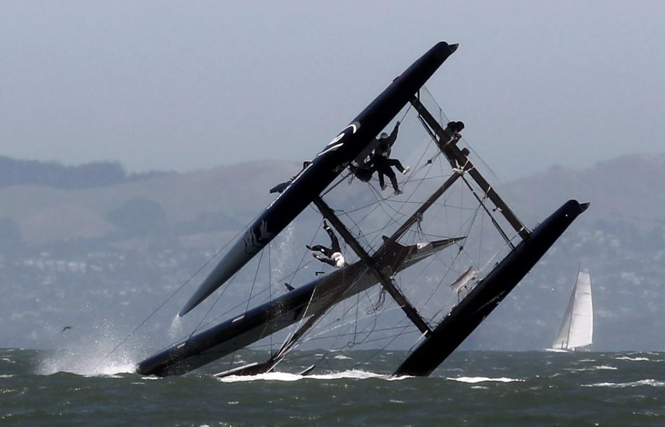 A sailor falls onto the wing of an Oracle Racing AC45 boat after it capsized during an exhibition race in San Francisco Bay