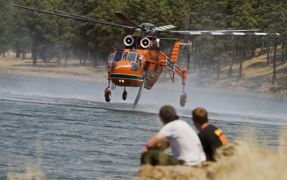 Wildland firefighters watch as a heavy helicopter fetches water from Luna Lake on the eastern edge of the Wallow Wildfire outside Alpine, Arizona