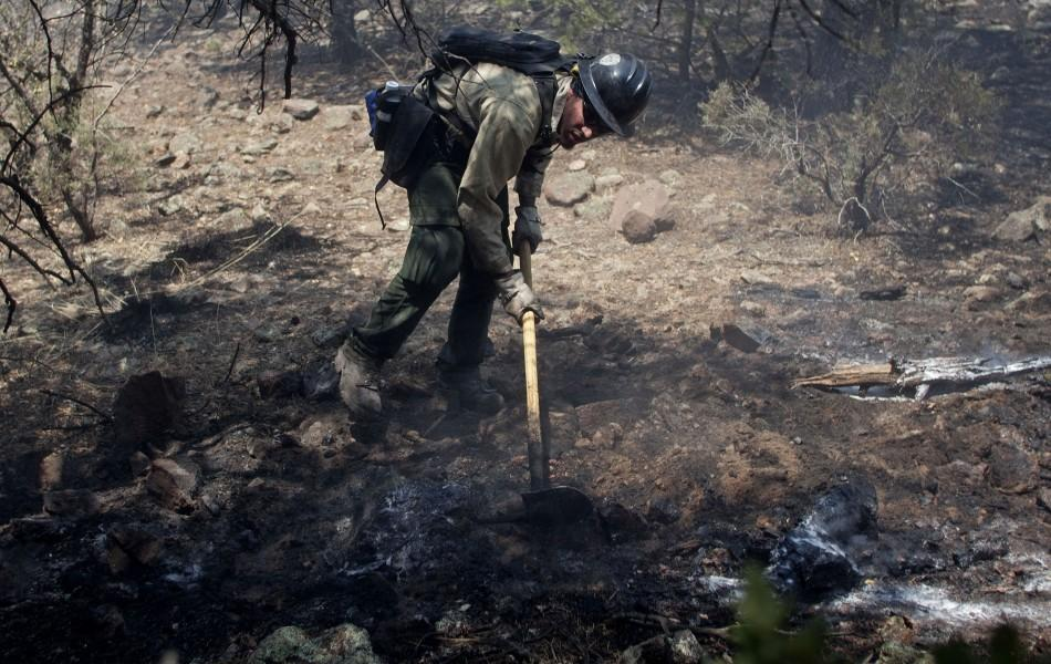 A wildland firefighter works at a hot spot on the eastern edge of the Wallow Wildfire outside Alpine, Arizona