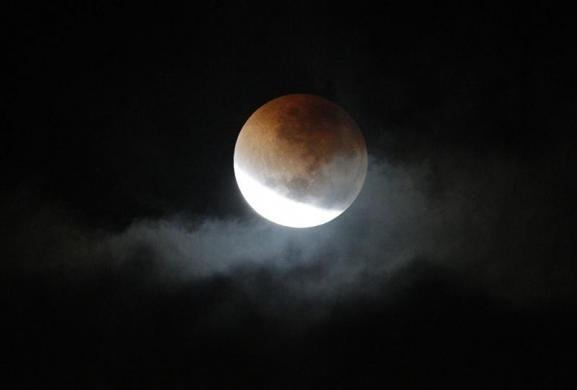 A lunar eclipse is visible through a gap in storm clouds over Sydney in the early hours of June 16, 2011.