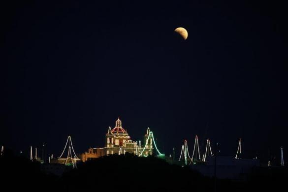 A partial lunar eclipse is seen over the village of Zejtun, lit up for its parish church feast of Saint Catherine, in the south of Malta June 15, 2011.