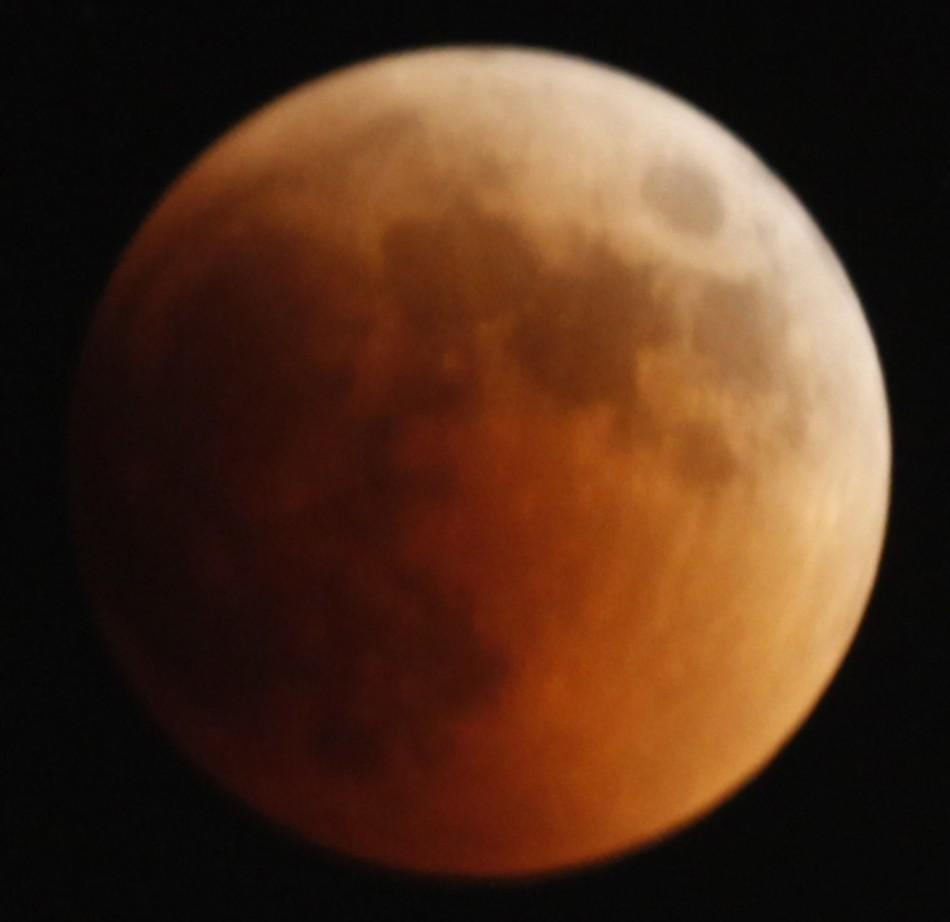 A shadow falls on the moon as it undergoes a total lunar eclipse as seen from Jerusalem