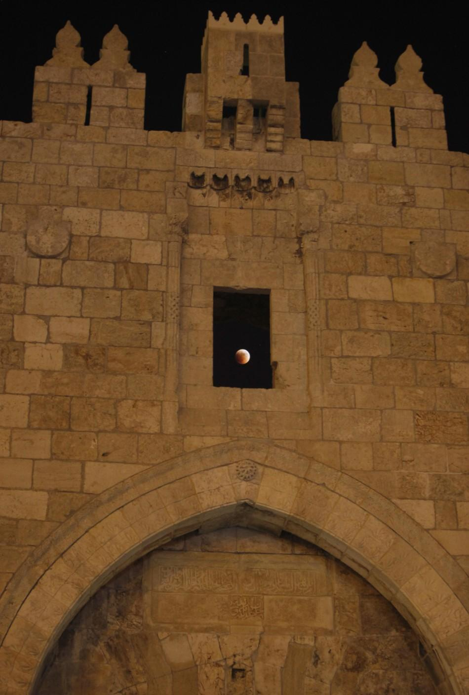 The moon is seen behind the wall of Damascus gate in Jerusalem old city during a total lunar eclipse