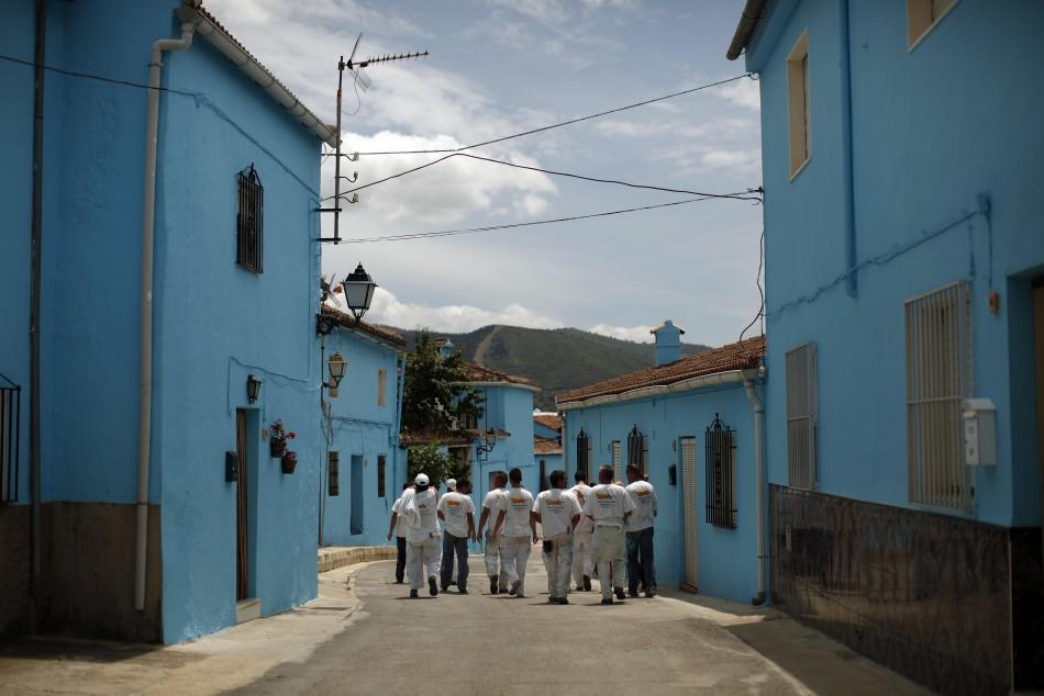 Painters walk along a street in Juzcar