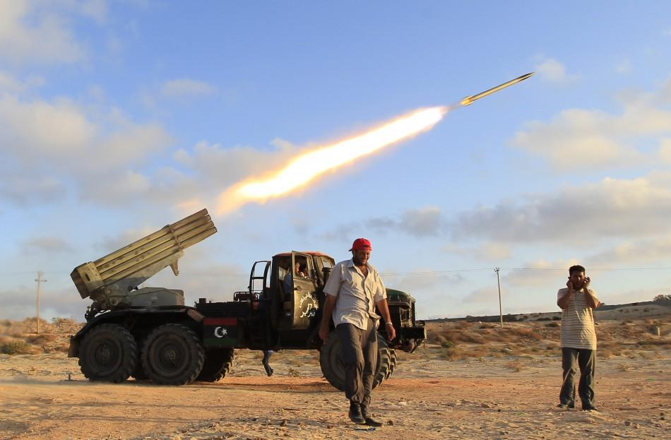 Libyan rebel fighters fire a grad rocket at the front line west of the rebel-held city of Misrata