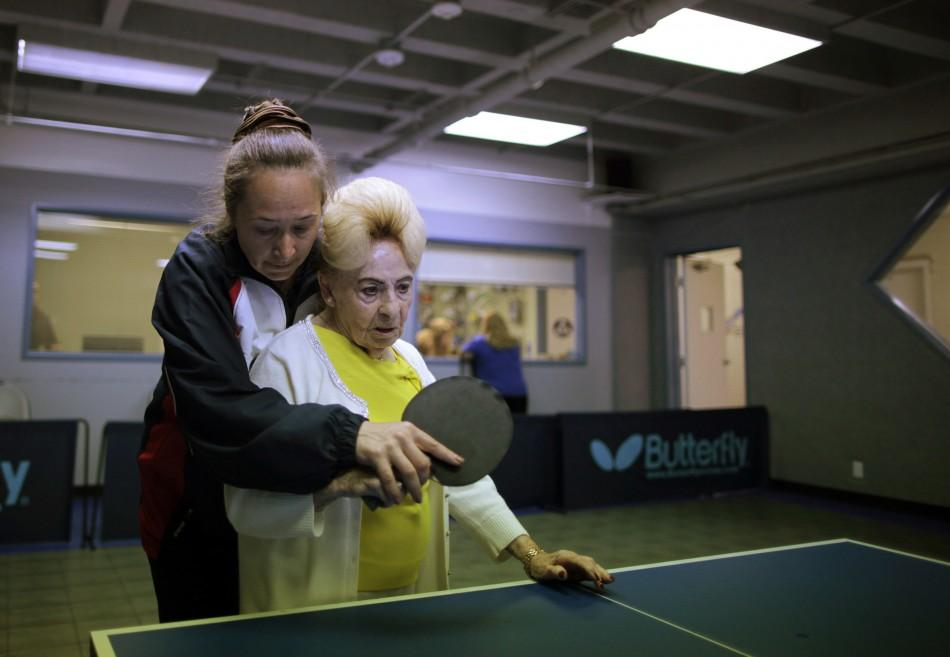 A holocaust survivor is helped by her coach as she plays ping pong at a program for people with Alzheimer's and dementia in Los Angeles