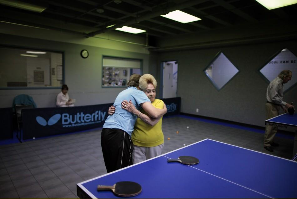 Holocaust survivor Betty Stein, 92, hugs coach Bella Livshin after playing ping pong at a program for people with Alzheimer's and dementia at the Arthur Gilbert table tennis center in Los Angeles