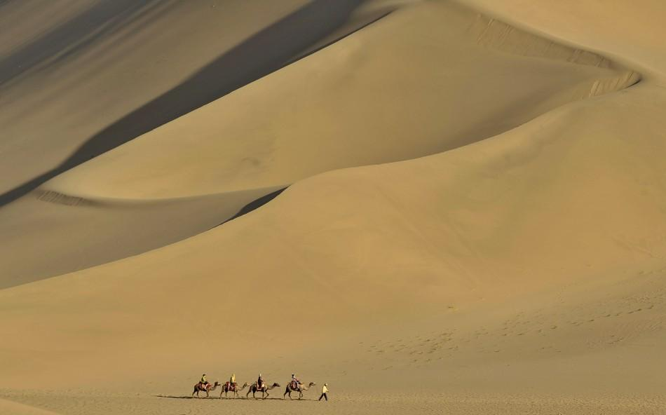 Tourists ride camels on the Mingsha Sand Dunes during a visit to Crescent Moon Spring on the outskirts of Dunhuang