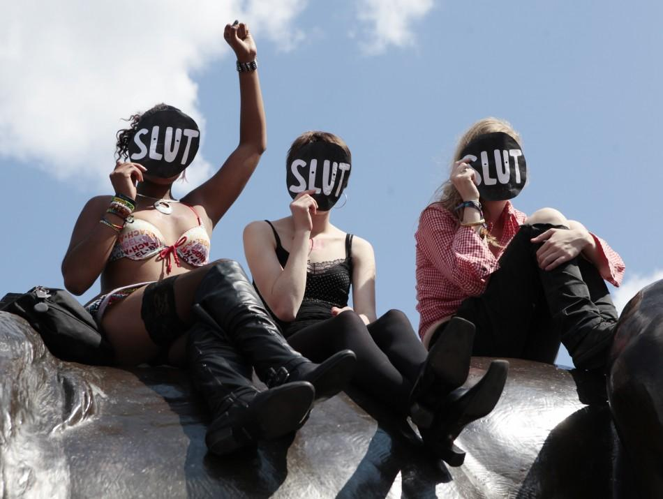 Women sit on a lion in Trafalgar Square during a rally after SlutWalk in London