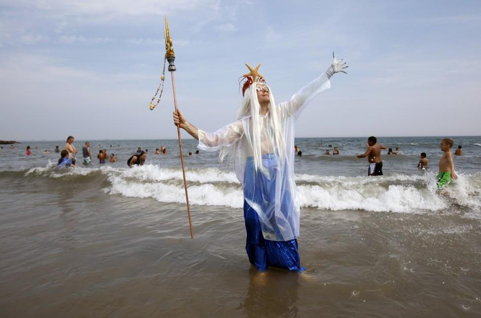 A man wades out of the water after marching during the Mermaid Parade at Coney Island in the Brooklyn section of New York