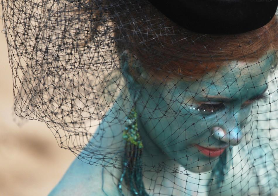A woman dressed as a mermaid sits on the beach after the Mermaid Parade at Coney Island in the Brooklyn section of New York