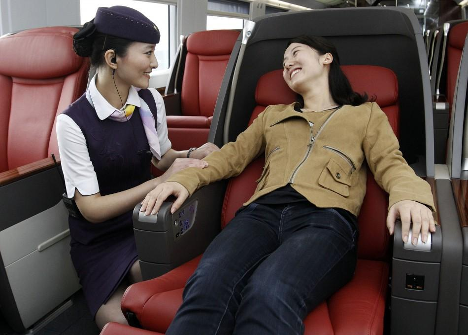 A train attendant helps a passenger on a train travelling on the newly built high-speed railway between Shanghai and Beijing during a test ride departed from Shanghai.