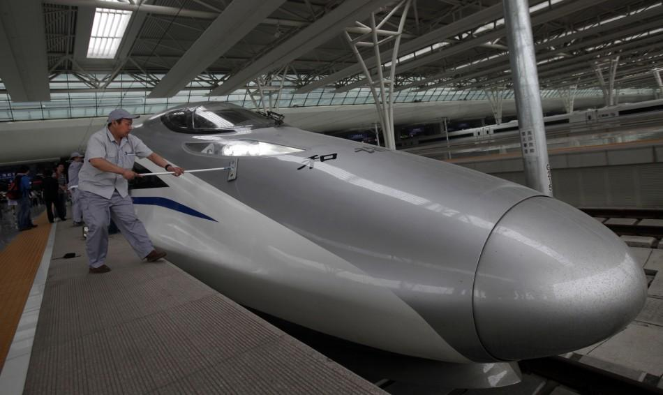 Workers clean the exterior of a CRH 380A bullet train serving the newly built high-speed railway between Shanghai and Beijing during its debut test at the Hongqiao Railway Station in Shanghai