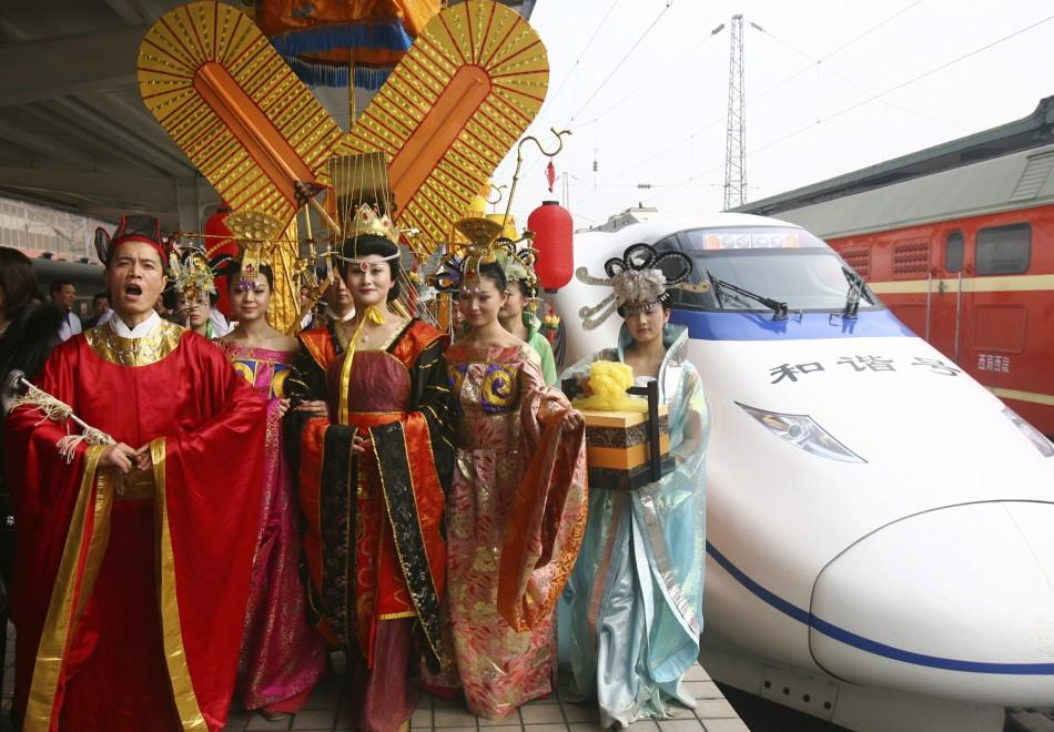 Actress dressed as China's first female emperor Wu Zetian and her entourage walk after their ride on the maiden journey of a high-speed train from Zhengzhou to Xi'an, Shaanxi province, to celebrate the start of the train service.