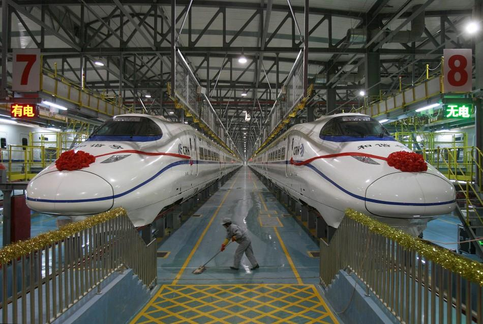 A labourer cleans the floor beside a China Railway High-speed (CRH) train preparing for the operation ceremony from Wuhan to Guangzhou in Wuhan, Hubei province, in this December 26, 2009