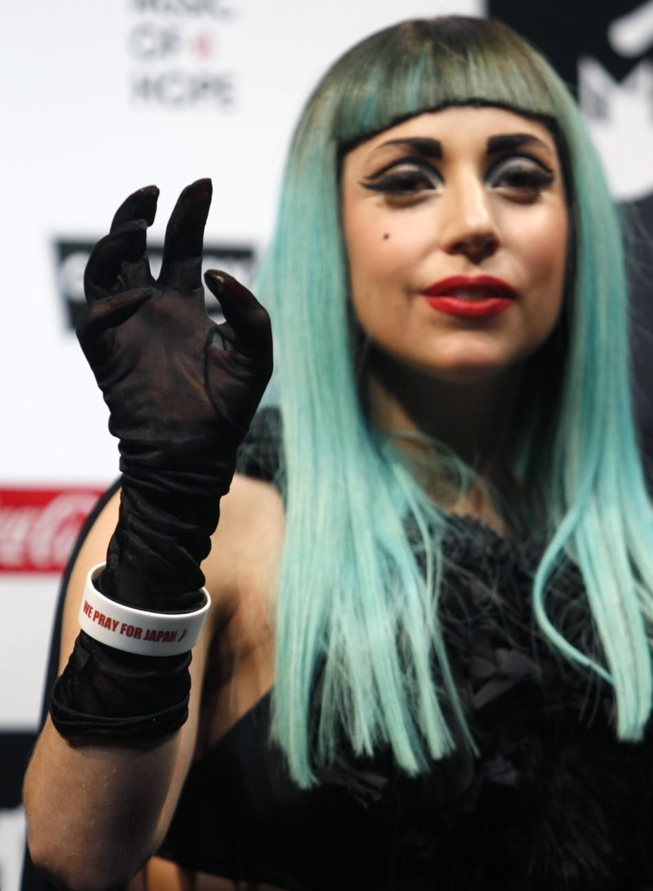"Lady Gaga, wearing an arm band written with ""We Pray for Japan"", gestures during a news conference in Tokyo"