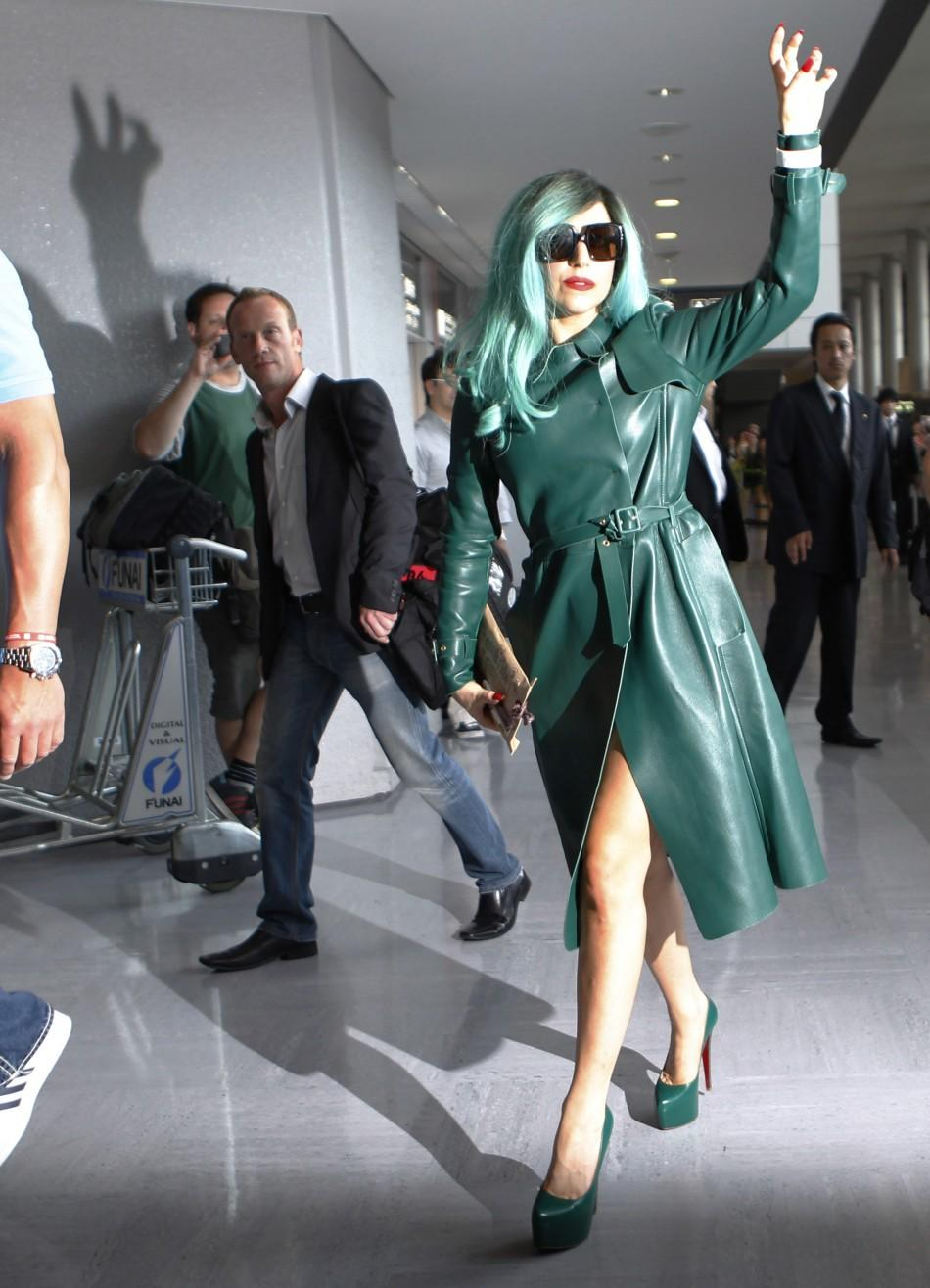 Singer Lady Gaga gestures at the media upon her arrival at Narita International Airport near Tokyo