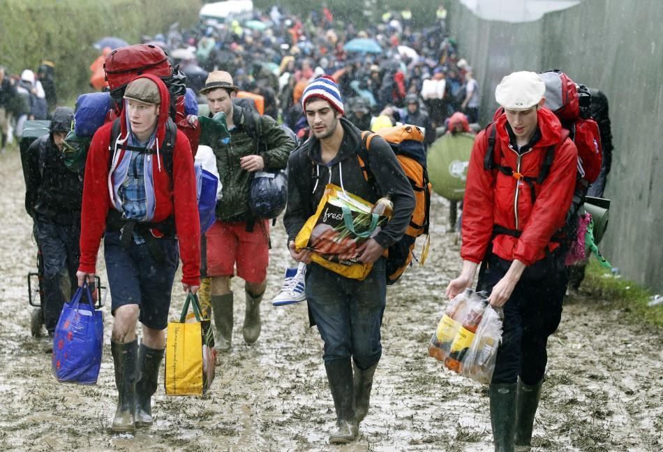 Glastonbury revelers get into festive spirits despite adverse weather conditions.