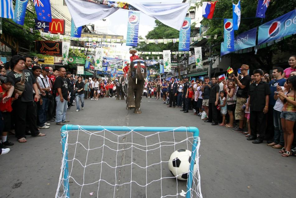Thai people and foreign tourists gather to see elephants play soccer at Bangkok's Khao San road