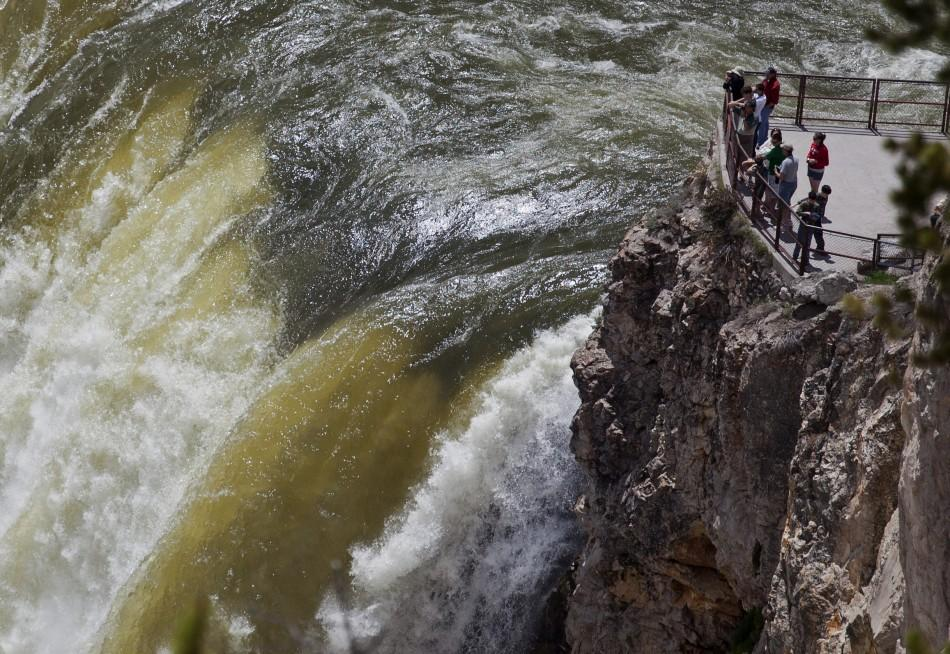 People stand at the brink of the 93-meter tall Yellowstone River Lower Falls in Yellowstone National Park