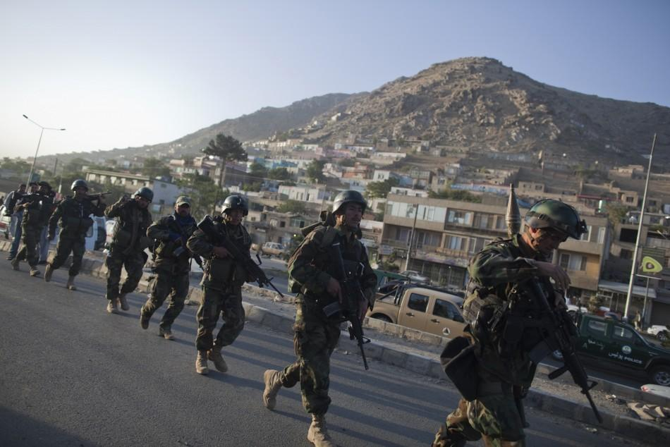 Afghan National Army soldiers march towards the Intercontinental hotel during a battle between Afghan security forces and suicide bombers and Taliban insurgents in Kabul