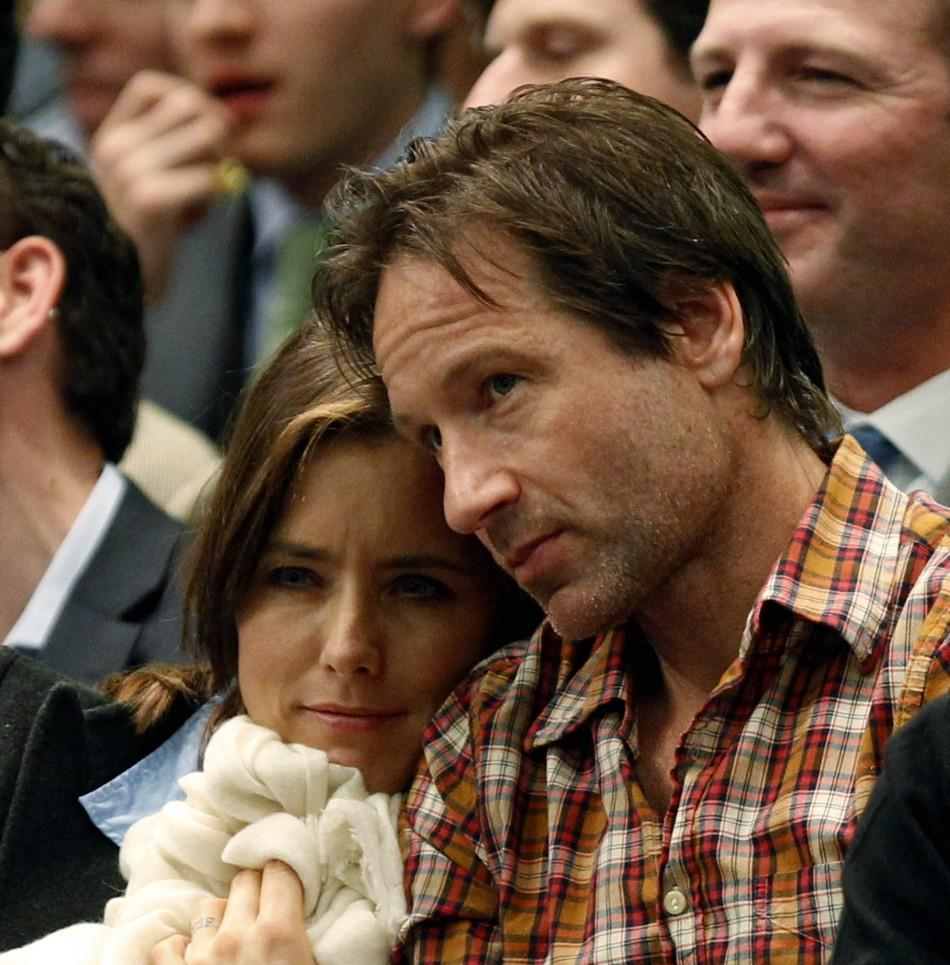 Actor David Duchovny sits with his wife, actress Tea Leoni, as they watch former world number one Andre Agassi and 14-time grand slam champion Pete Sampras play their exhibition match at the BNP Paribas Showdown at Madison Square Garden in New York Februa
