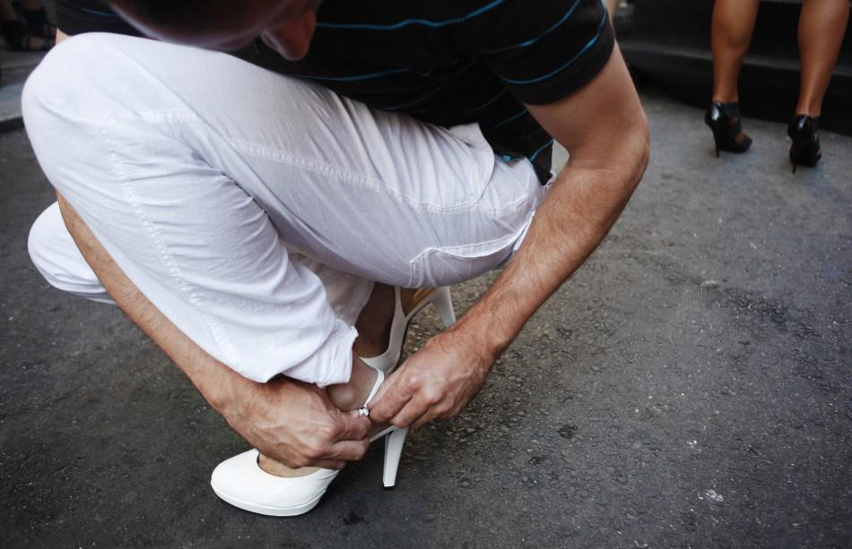 A man puts on his high heel shoes before the annual race on high heels during Gay Pride celebrations in the quarter of Chueca in Madrid