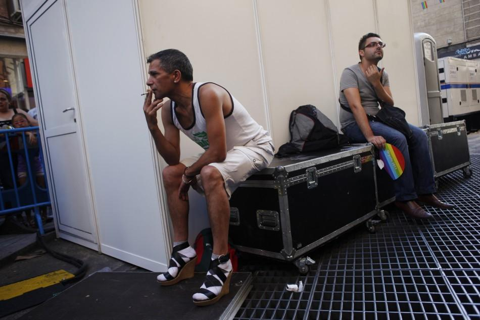 A man smokes with his high heel shoes on as he waits to take part in the annual race on high heels during Gay Pride celebrations in the quarter of Chueca in Madrid