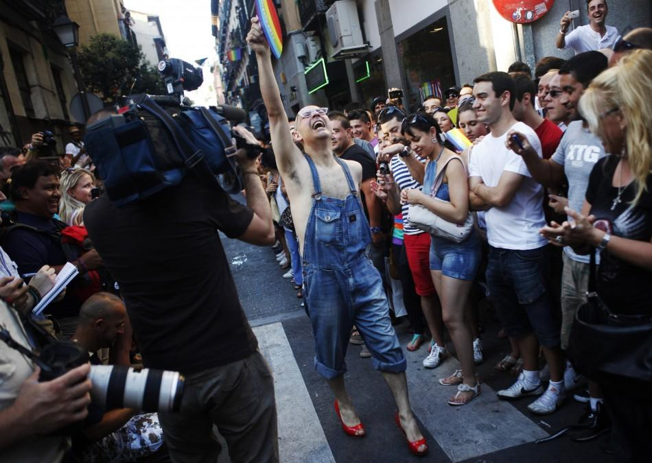 A contestant celebrates finishing the annual race on high heels after losing one of his shoes at the start of the race during Gay Pride celebrations in the quarter of Chueca in Madrid