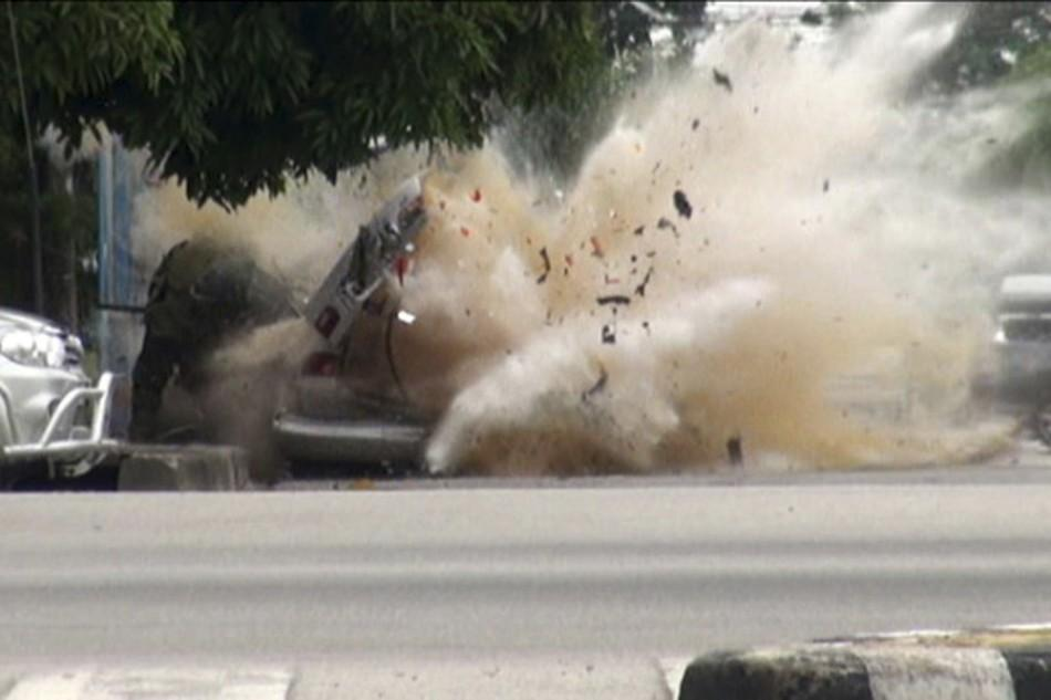 A car bomb explodes as a member of a Thai bomb squad checks it in Narathiwat province