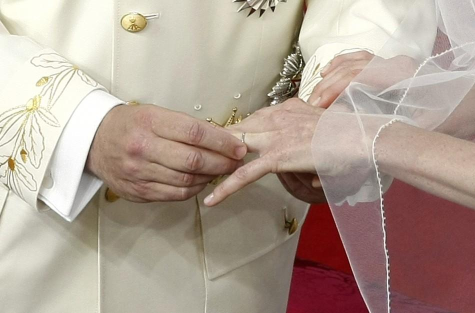 Prince Albert II of Monaco puts the wedding ring on the finger of his bride Princess Charlene during their religious wedding ceremony