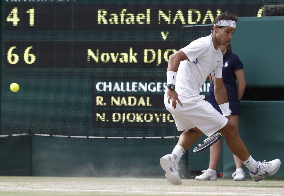 Rafael Nadal of Spain attempts to hit a return through his legs during his men's singles final match against Novak Djokovic of Serbia at the Wimbledon tennis championships in London.