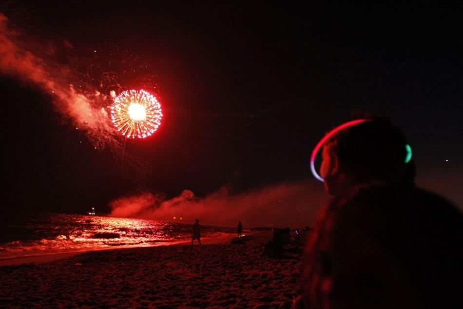 A boy watches fireworks during holiday celebrations held on the eve of Fourth of July at Atlantic Beach