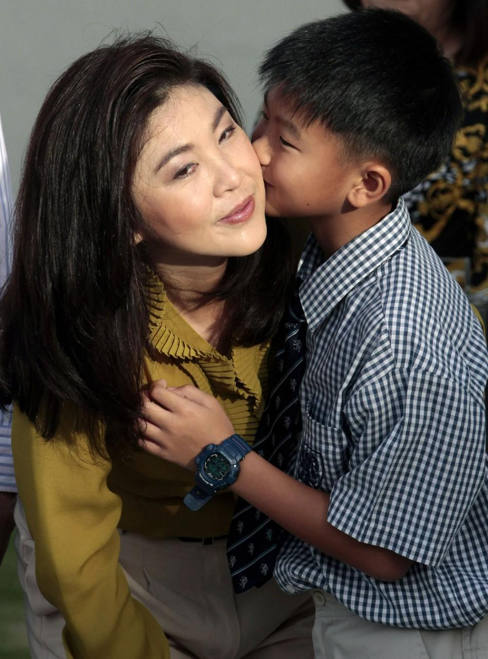 Supasek Amornchat kisses his mother Yingluck Shinawatra