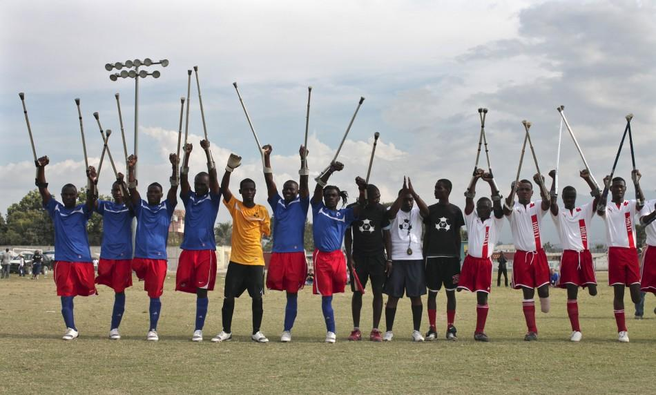 Haitian soccer players of the Zaryen team (blue) and the national amputee team (white) greet the crowd before a friendly match in Port-au-Prince