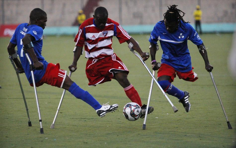 Soccer players from Haiti's Zaryen team and the national amputee team fight for the ball during a friendly match in Port-au-Prince