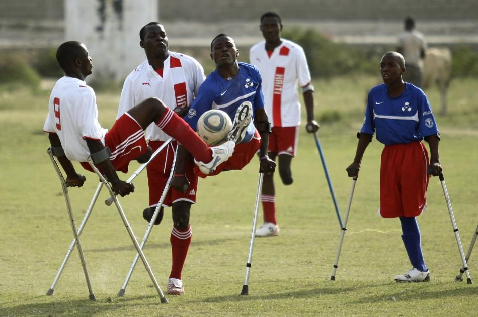 Haitian soccer players of the Zaryen team and the National amputee team fight for the ball during a friendly match in Port-au-Prince