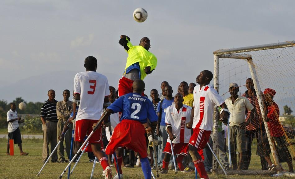 Haitian national amputee team goalkeeper stops the ball from players of the Zaryen team during a friendly match in Port-au-Prince