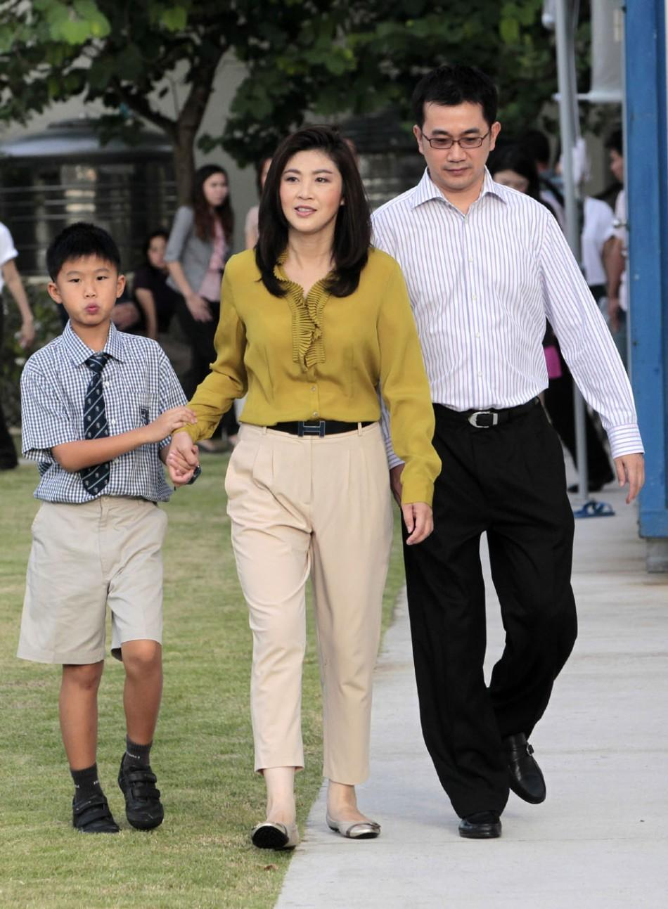 Yingluck Shinawatra walks with husband and son