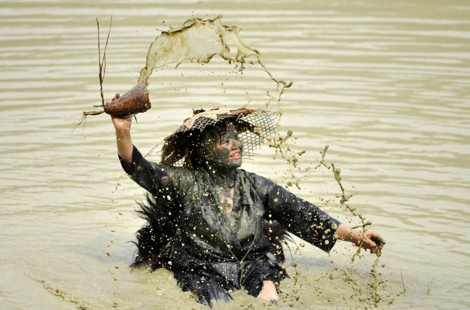 A woman splashes water with a container as she performs the Shuigu dance during a cultural festival in Jianhe county, Guizhou province July 6, 2011. The dance, which is also known as the water drum dance, has a history of over 500 years in local Miao vill