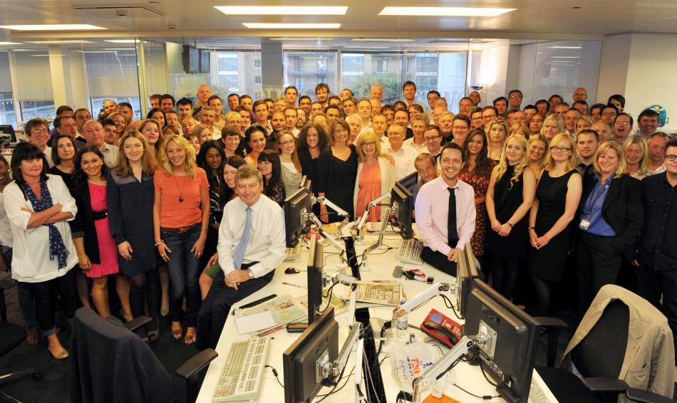 The News Of The World editor Colin Myler poses for a photograph with the staff of the newspaper in their newsroom in London