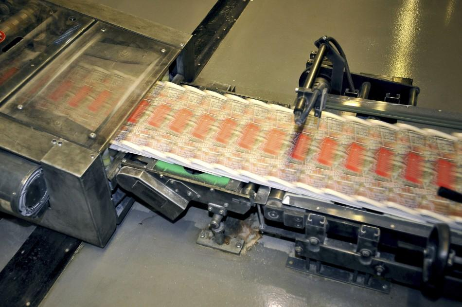 Copies of the final edition of the News of the World are printed on the presses at the News International print works in Waltham Cross, southern England