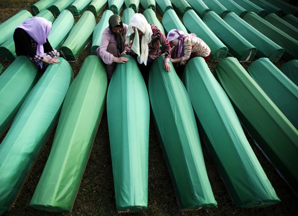 Women mourn in front of coffins prepared for a mass burial at the Memorial Center in Potocari, near Srebenica