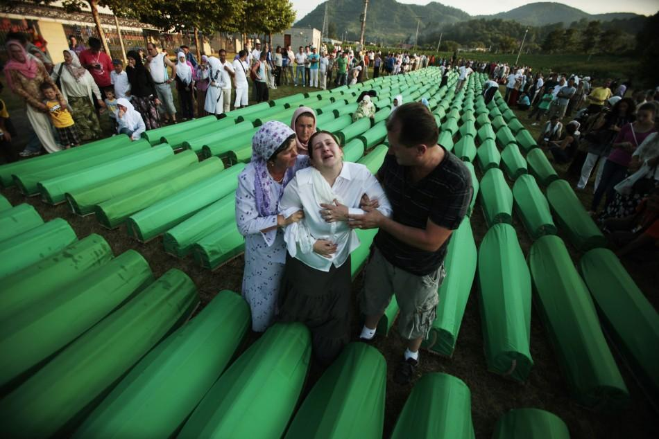 Bosnian Muslims cry near coffins prepared for a mass burial at the Memorial Center in Potocari, near Srebenica