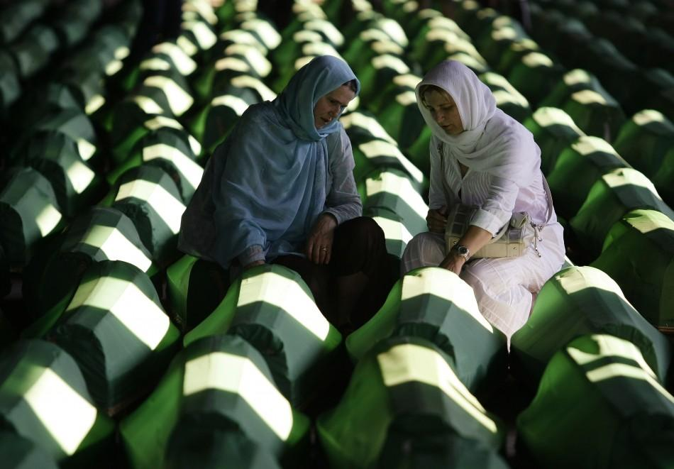 Woman mourn in front of coffins prepared for a mass burial at the Memorial Center in Potocari, near Srebenica