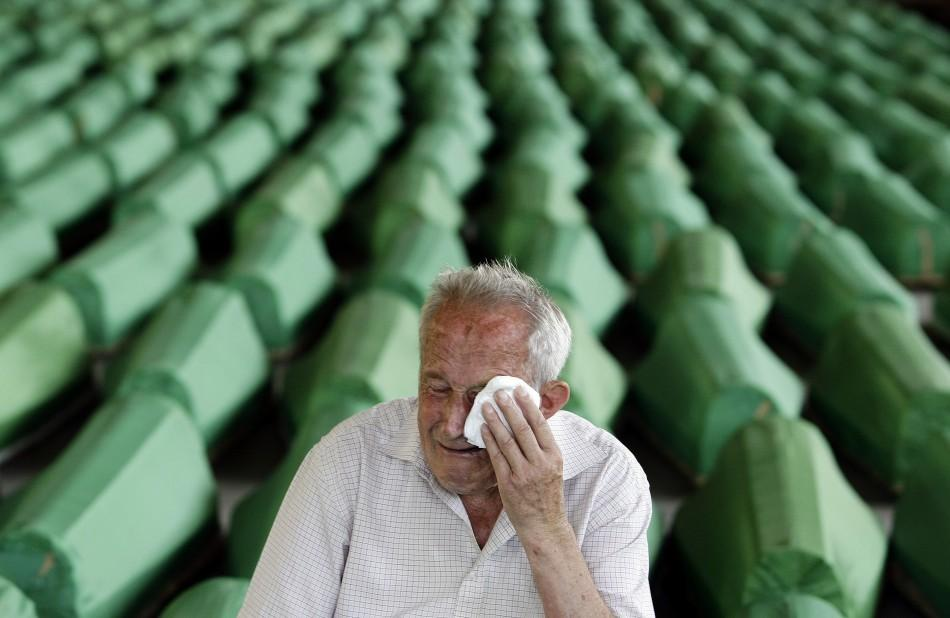 A man mourns in front of coffins prepared for a mass burial at the Memorial Center in Potocari, near Srebenica
