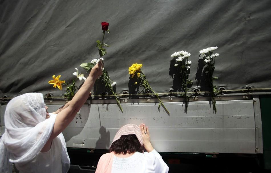 Bosnian women put flowers on one of the trucks carying 614 coffins of newly identified victims of the 1995 Srebrenica massacre in front of the presidential building in Sarajevo