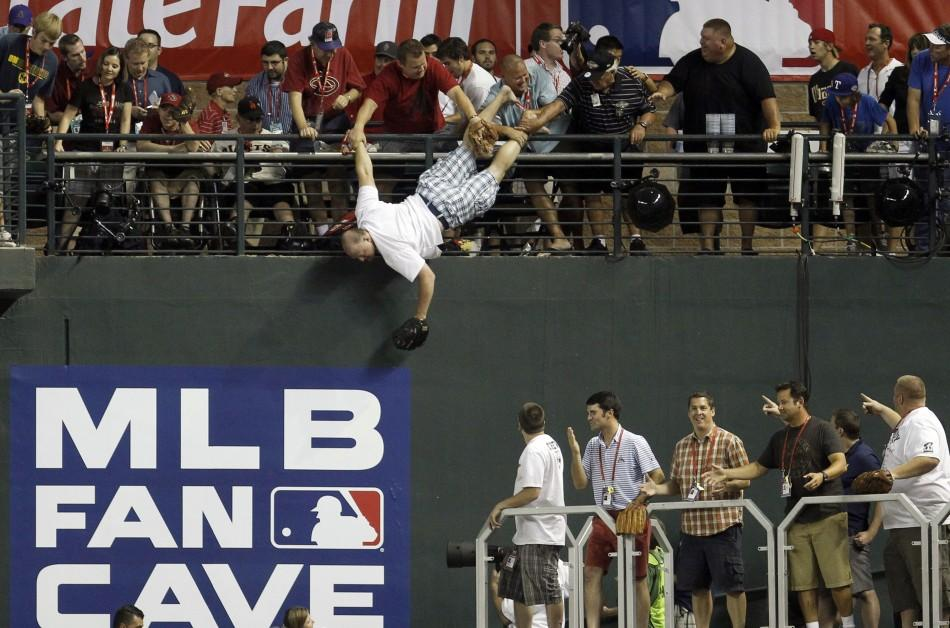 A man is caught after he almost fell headfirst to a pool deck about 20 feet below while trying to catch home run ball during Major League Baseball's Home Run Derby at the All-Star Game in Phoenix